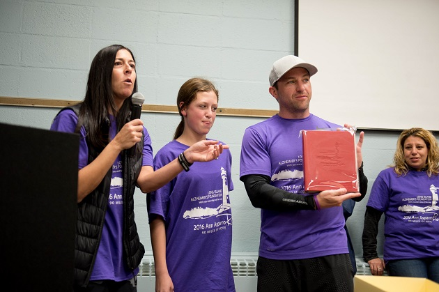 """Tori Cohen (far left), Executive Director of Long Island Alzheimer's Foundation, presents Jay Asparro (far right) with a photo album book to collect the numerous memories and photos of the Inaugural """"Ann Asparro Run."""" Asparro completed his three-day, 90-mile Multi-Marathon Inaugural """"Ann Asparro Run"""" to honor his grandmother and raise Alzheimer's Awareness as well as funds for Long Island Alzheimer's Foundation to make a difference in the lives of others suffering from this disease or other memory disorders. Photo credit: Rob Loud."""