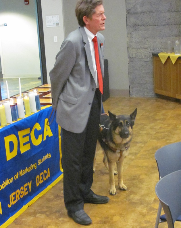 Dr. James A. Kutsch Jr., the President of Seeing Eye, Inc., speaking at an event for a high school organization called DECA.